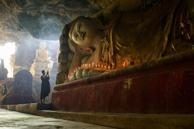 Asian monk lighting incense in temple by Gable Denims