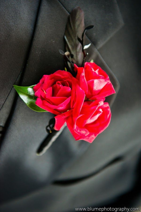 Verizon Amphitheatre Wedding - One Is Not Enough Wedding Tour - Boutonniere of Red spray roses & black feathers- | floral by anik designs  - photos by Blume Photography