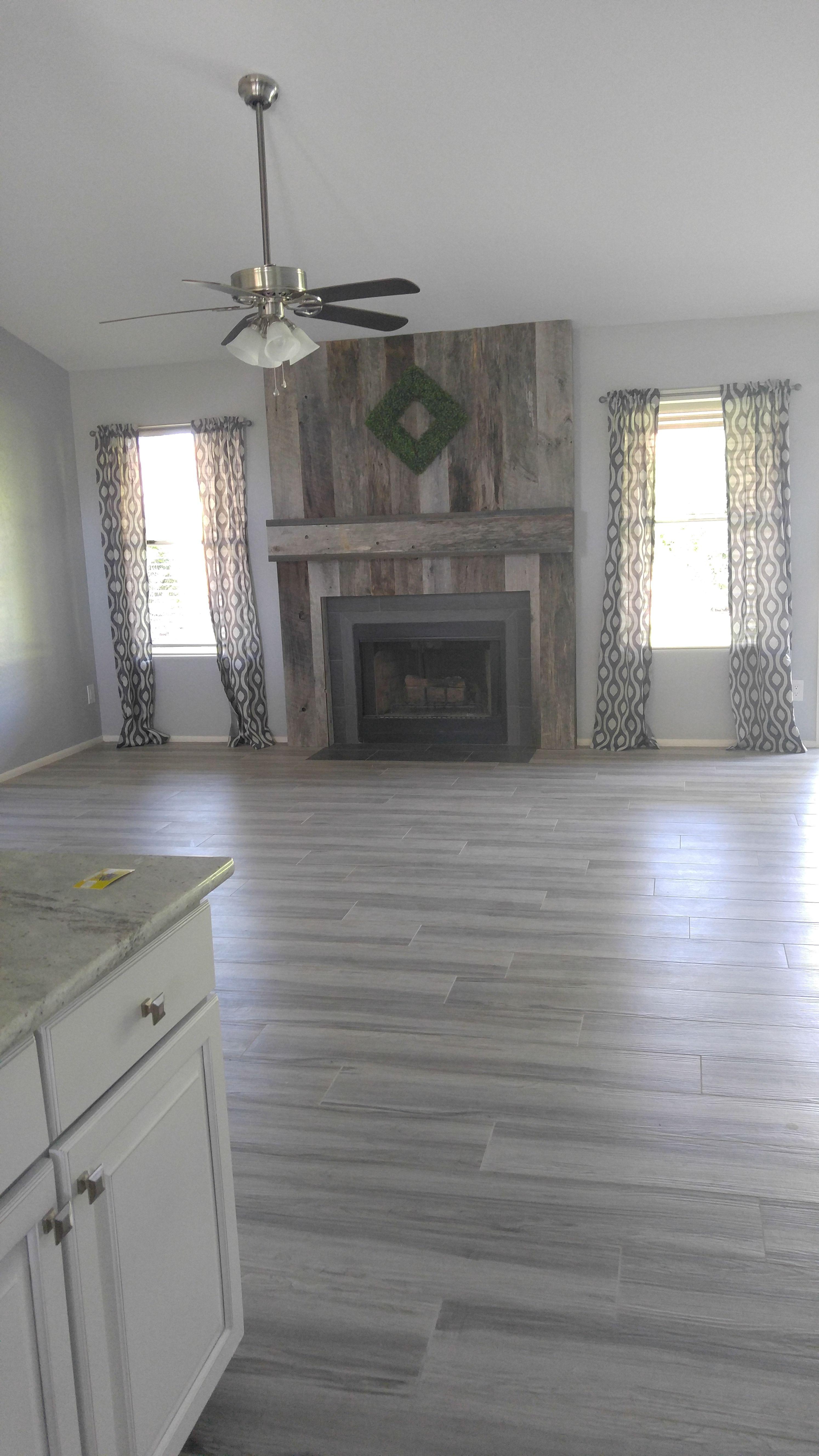Gray wood look tile flooring. Reclaimed wood fireplace