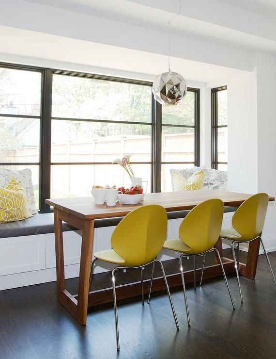 Modern Breakfast Nook Window Seat Features A Built In Bench Facing Wood Dining Table Lined With Yellow Plastic Chairs Illuminated By