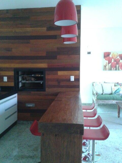 Parede da churrasqueira em madeira de demolição. Bancada madeira maciça antiga.banquetas e luminárias vermelhas