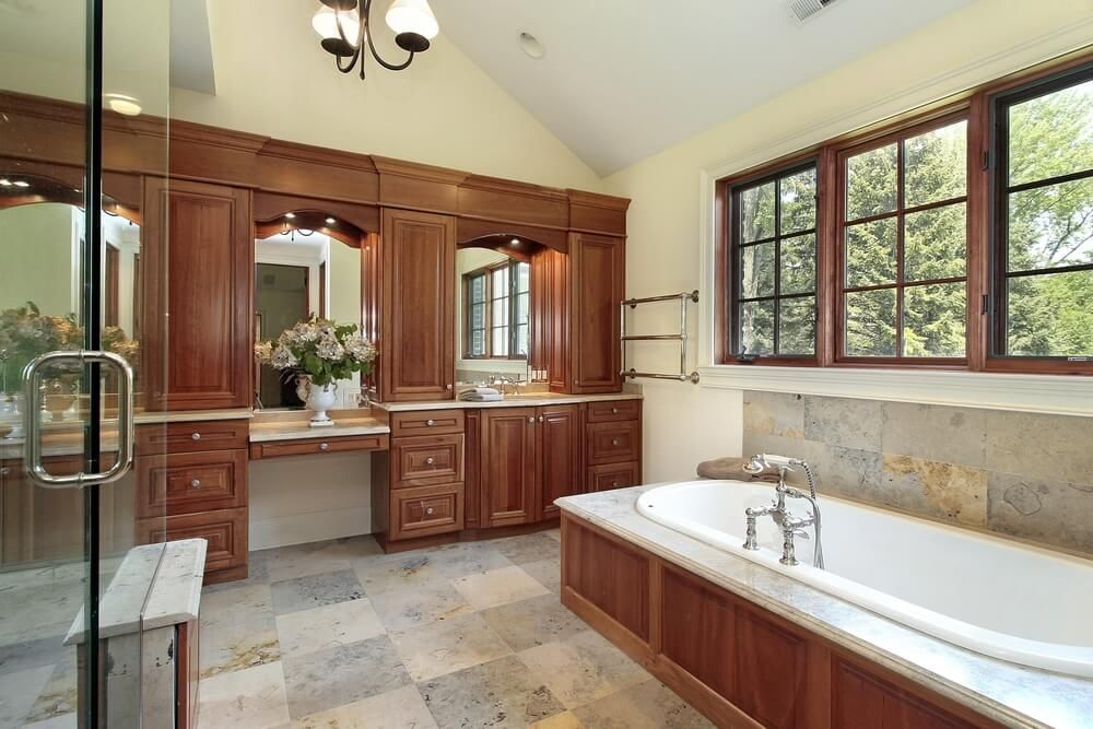 Subtly checkered marble flooring supports an expanse of natural wood throughout this master bathroom, including wall-length vanity with large upper cabinets and marble topped bathtub surround across from glass shower.