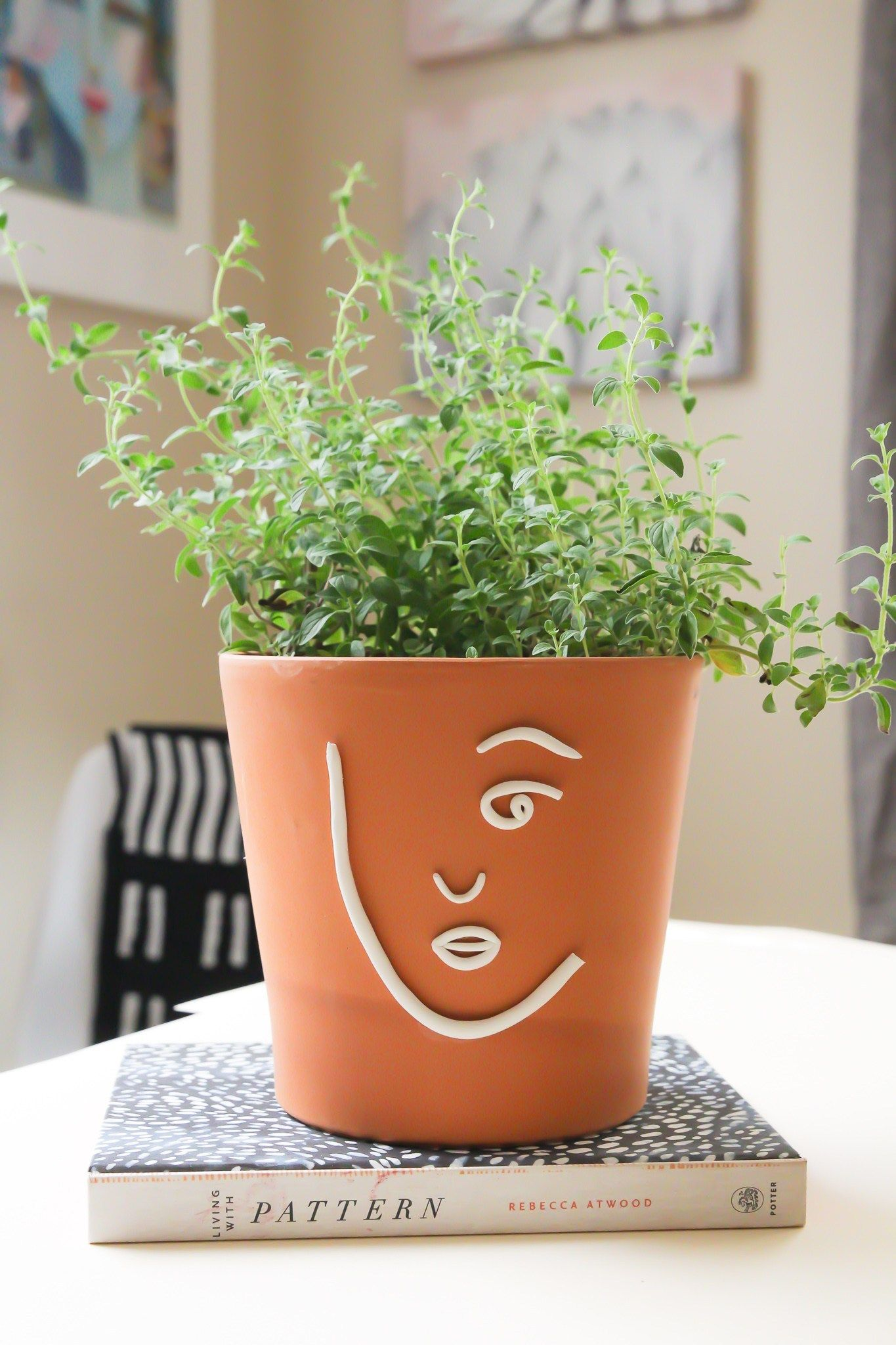 This minimal clay pot craft is easy to make. Use polymer clay to make a face then glue the clay to a terra-cotta pot. Its the perfect craft to relax with! #claypotpeople #clayprojects #pottery #planter