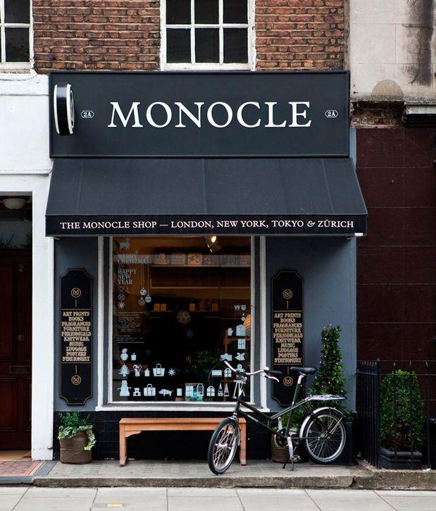 Toldo negro coordinado con fachada y rotulo monocle store for Toldos para negocio