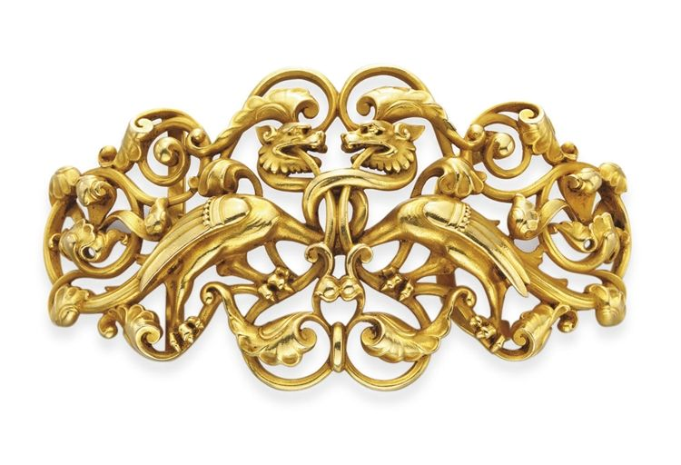 AN ANTIQUE RENAISSANCE-REVIVAL GOLD BELT BUCKLE  -  Designed as an openwork tapered 18k gold buckle depicting two griffins with foliate and scrolling detail, 19th century.