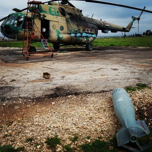 RBK 250-275 cluster munitions dispenser that the Syrian Air Force did not manage to use. Taftanaz Air Base, 2013. Syria. Captured Mi-8 series helicopter in background.