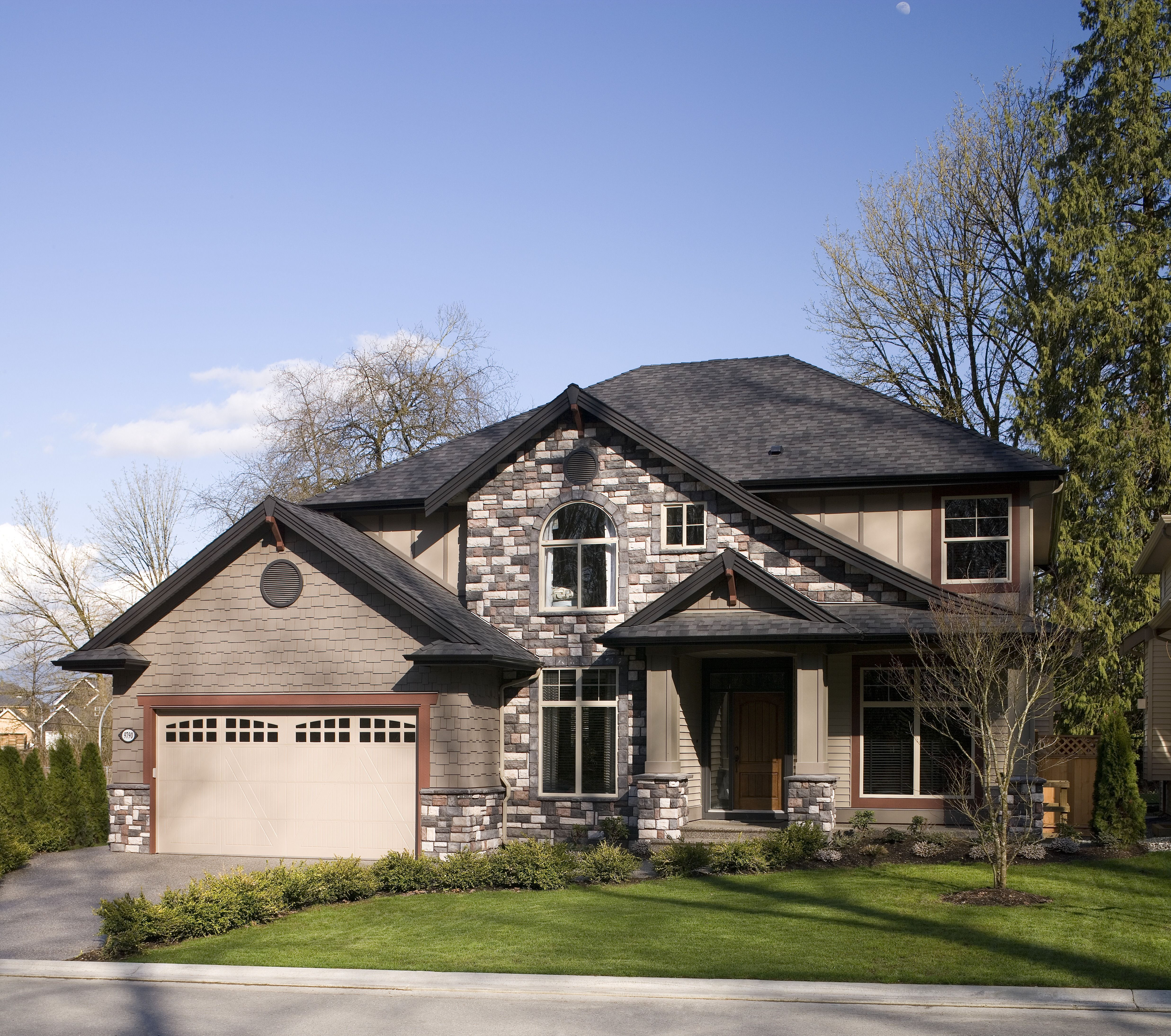 Large two story house with a manicured lawn a combination for Houses with stucco and siding