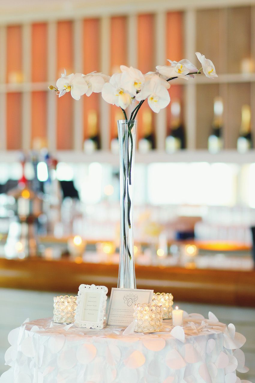 Orchids in Long-Necked Glass Vases | Photography: Vanessa Joy Photography. Read More: http://www.insideweddings.com/weddings/a-bright-modern-summer-wedding-with-mint-coral-details/648/