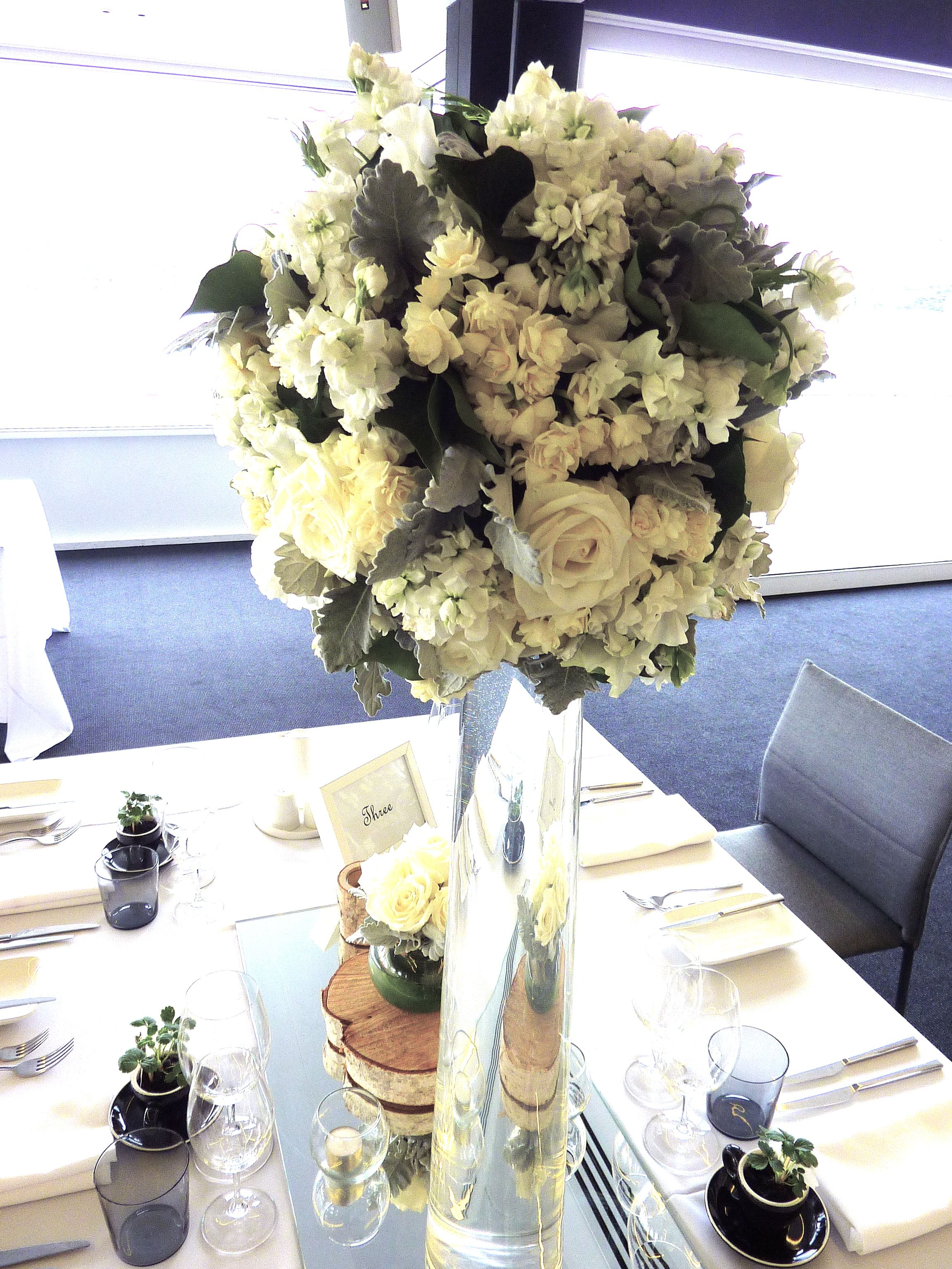 Tall vases with lush flower ball on alternate guest tables, would have coral in it