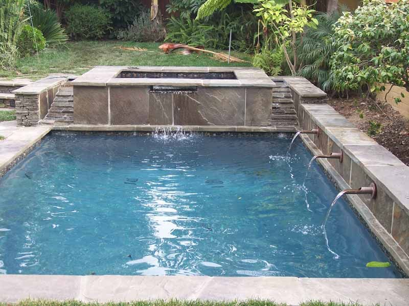 rectangular pool with raised jacuzzi and pipe and step water feature