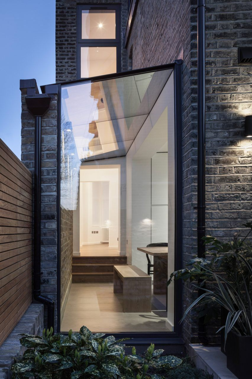 Mulroy architects has added a glass passageway to the side of this three storey house in north london which features an interior fitted with bespoke oak