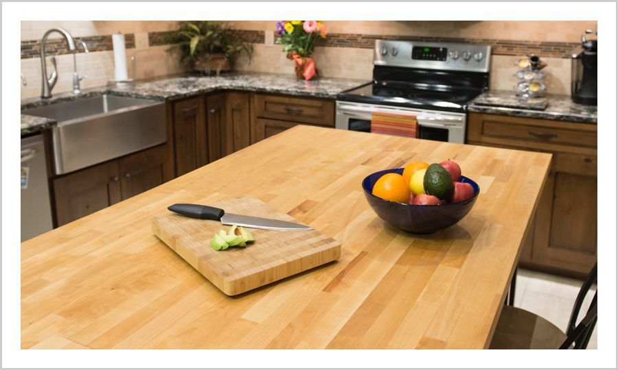 Butcher Block Island With A Fruit Bowl On Top In A Kitchen With