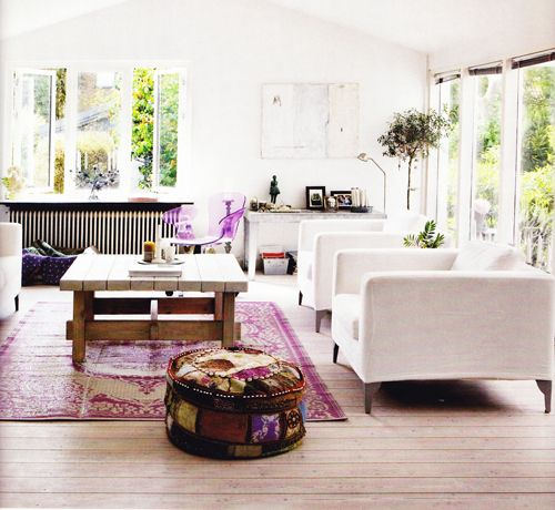 Pretty bohemian chic living space. Purple Persian rug, embroidered Indian pouf, chestnut floorboards & modern white arm chairs. This open space oozes serenity.