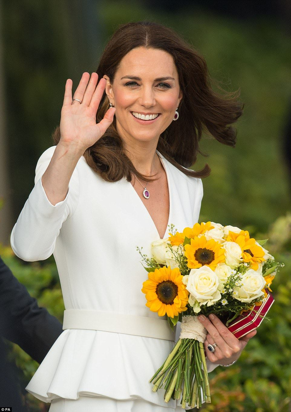 The Duchess of Cambridge waves to the crowd as she leaves the Spire Building, Warsaw, foll...