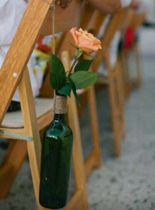 Wine bottle vases on chairs.