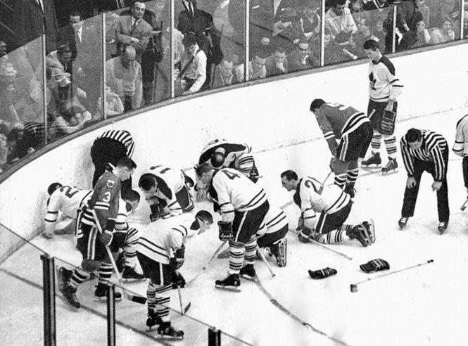 Jugadores de los Black Hawks de Chicago y Maple Leafs de Toronto buscando un lente de contacto que ... - #foto #história #hockey #lente