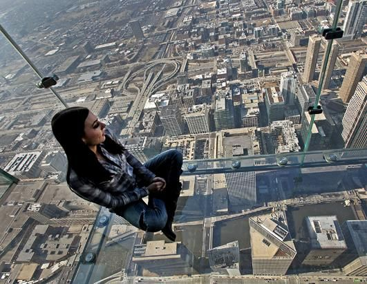 A girl sits on the glass balcony at the skydeck of the willis tower in chicago