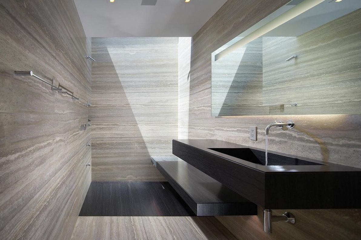 Travertine walls with what looks like a nero absolute honed finish