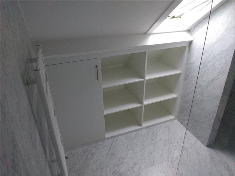 Witte kast, precies op maat gemaakt onder een schuin dak. De ...