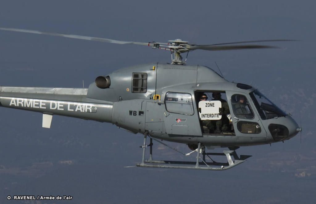 """French Arméee de l'Air Eurocopter AS550 Fennec (Desert Fox). This is the subtle version of what you might see if you stray into an exercise zone in France. The crewman holding sign that says """"Zone Interdeit"""" - Forbidden Area."""