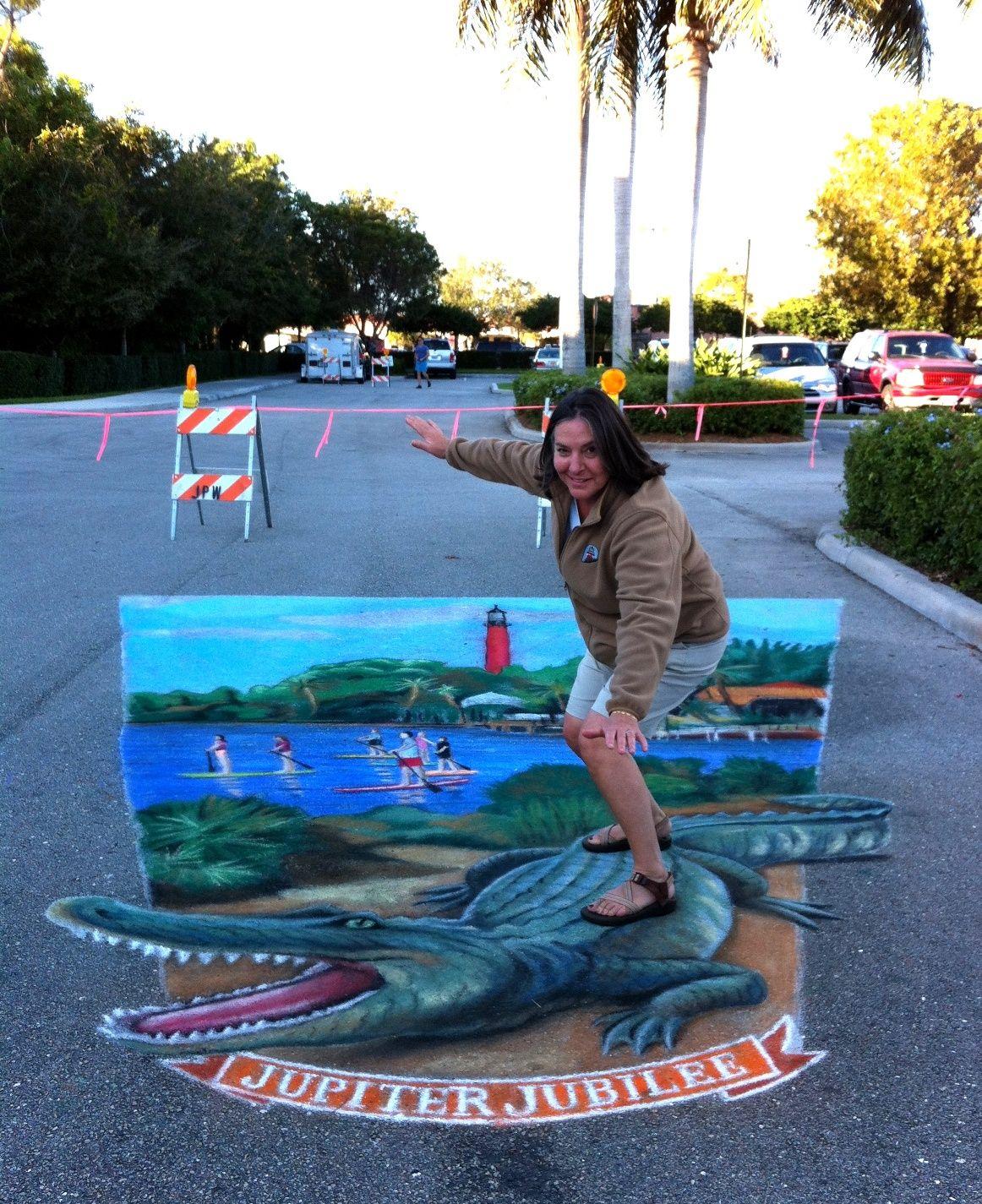 "Ann ""riding"" the 3D alligator - chalk art at Jupiter Jubilee 2013 by AmazingStreetPainting.com"