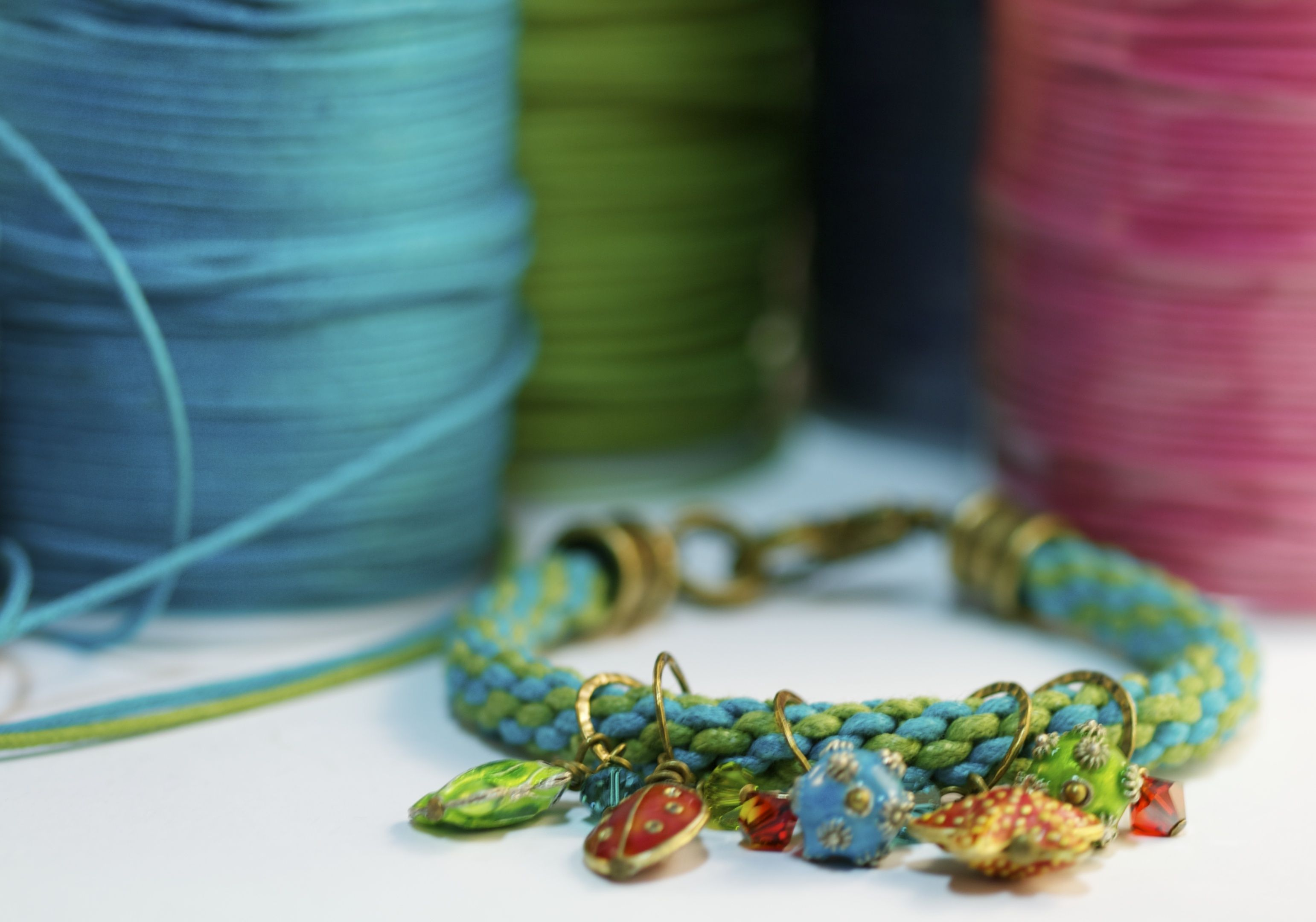 We love waxed cotton cording and the many uses for it! Kumihimo style with cloisonné charms!