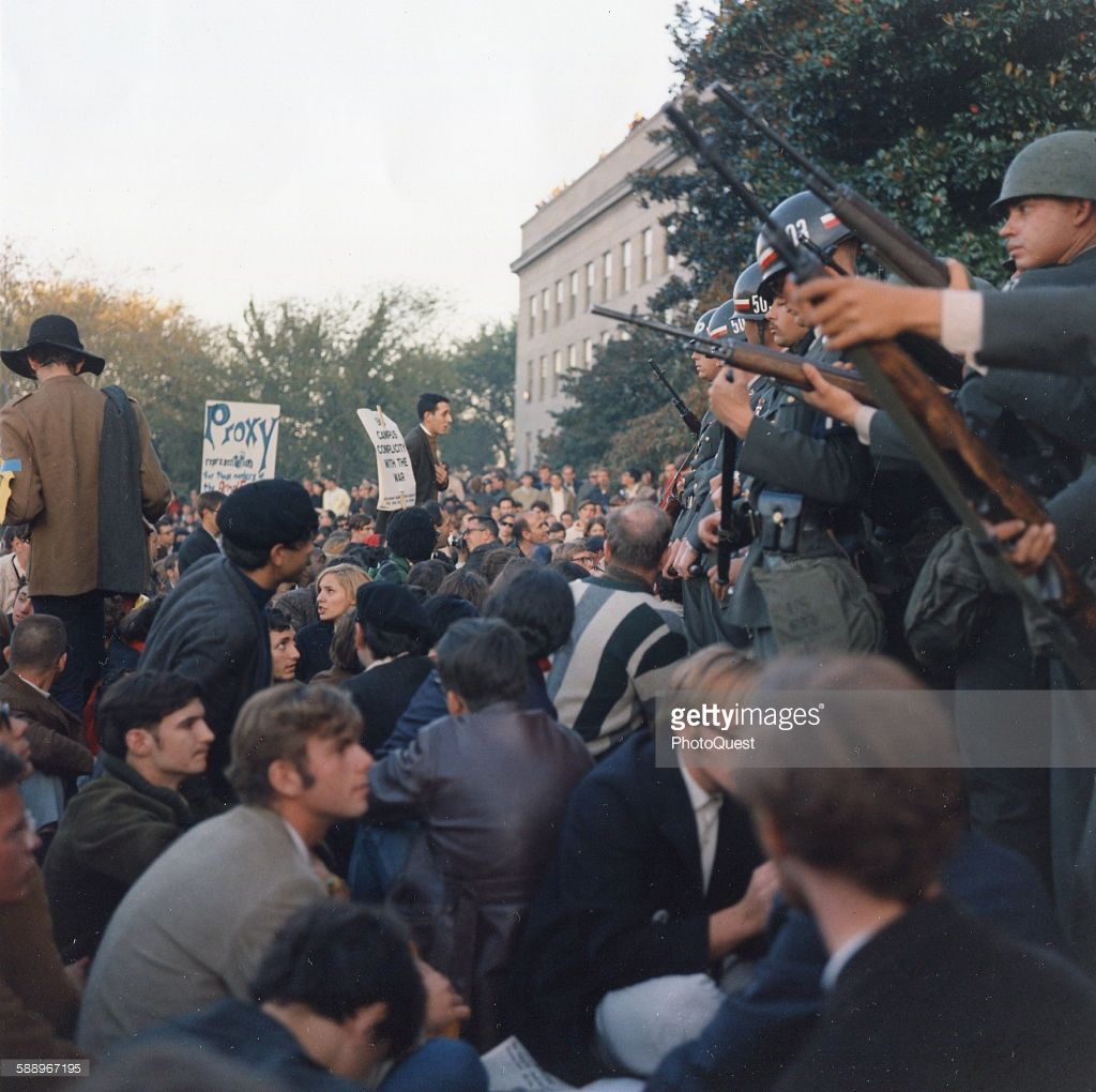 Members of the Military Police stand guard over protestors during a sit-in at the Mall entrance to the Pentagon, Washington DC, October 11, 1967.