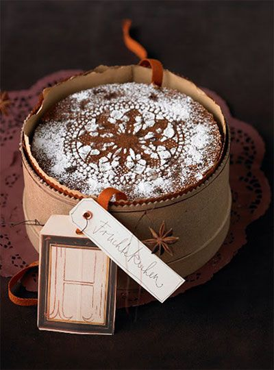 What a lovely, personal touch ... using a paper doily to sprinkle confectioners sugar onto a Christmas cake.  Tucking it into a vintage hatbox makes it doubly elegant.  -- Eve.