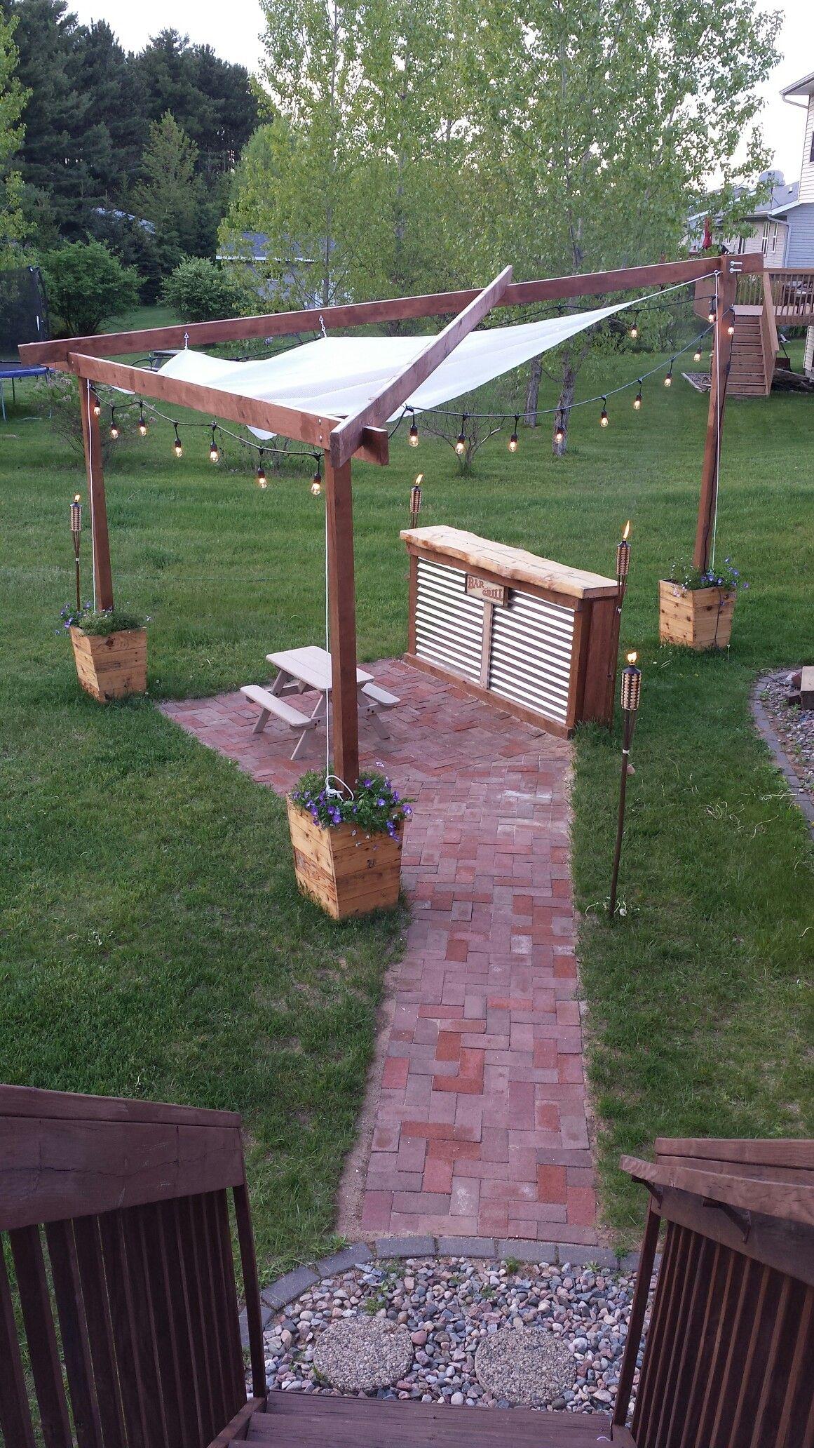 Brick patio cedar planter boxes shade sail string lights back
