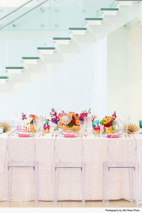 Photography: Elle Rose Photo  Venue: Colorful wedding reception table with lace  tablecloth, pink napkins, and botanical flower arrangements set against a glass staircase | Chez Chicago Wedding Venues