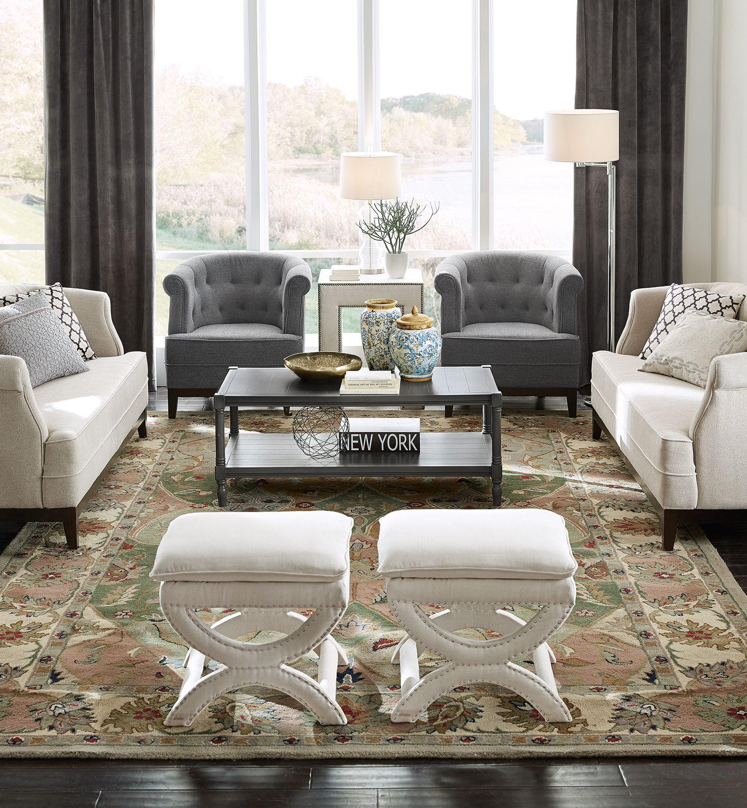Create a sophisticated seating arrangement with neutrals and grey matched with tufts and nailhead trim. Position furniture in a way that's inviting and accommodating to family and friends when entertaining.