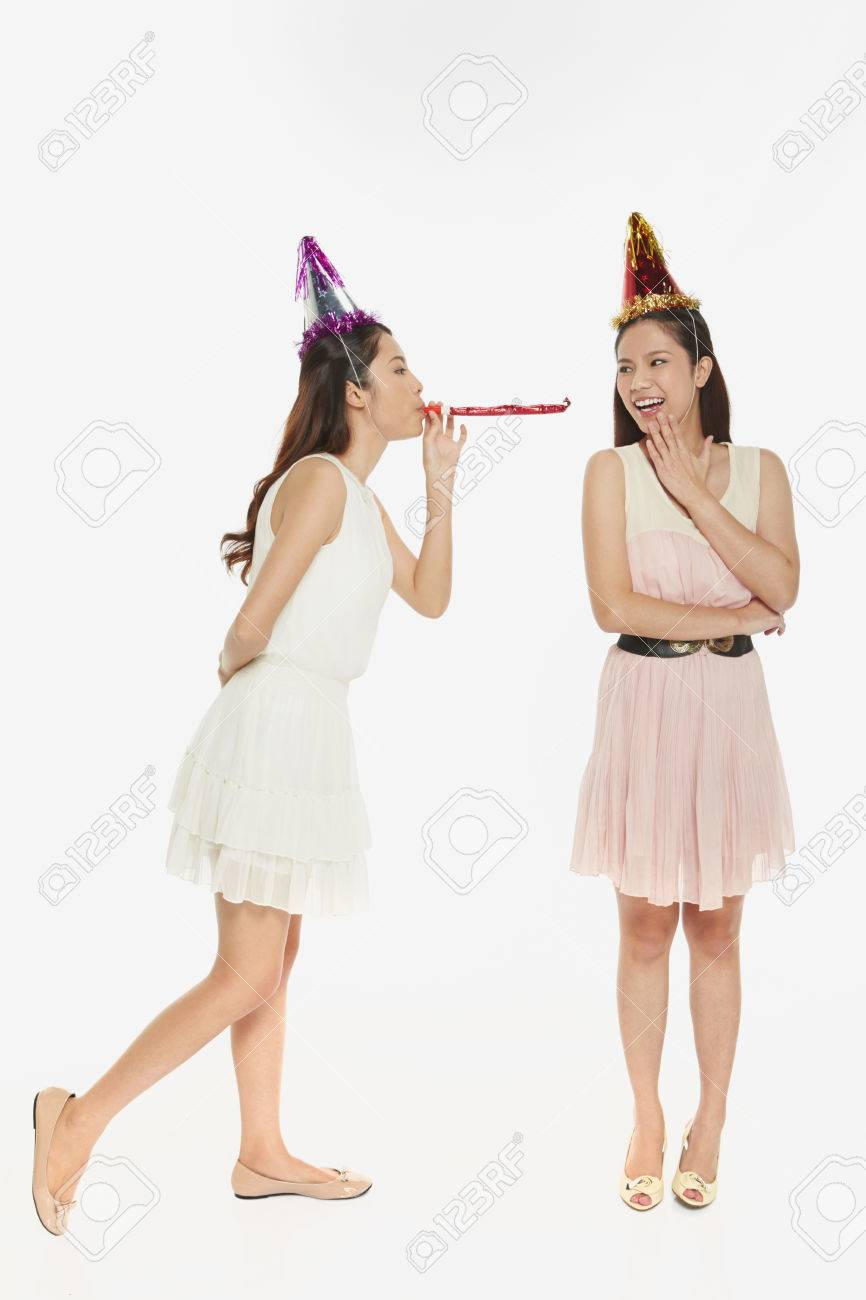 Woman Blowing The Party Horn Blower At Her Friend Stock Photo 22838869 Party Horns Women Flower Girl Dresses