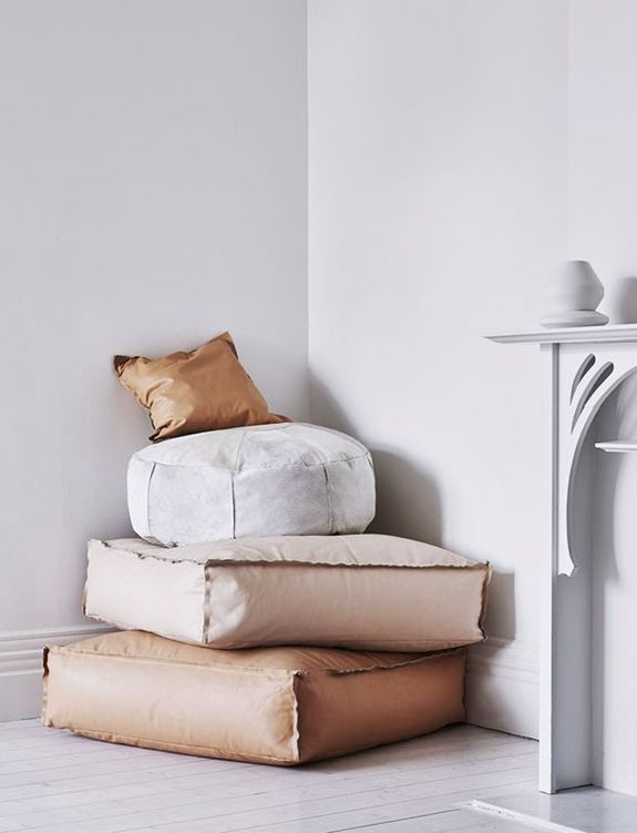 leather floor cushions stacked in corner of whitewashed space. / sfgirlbybay