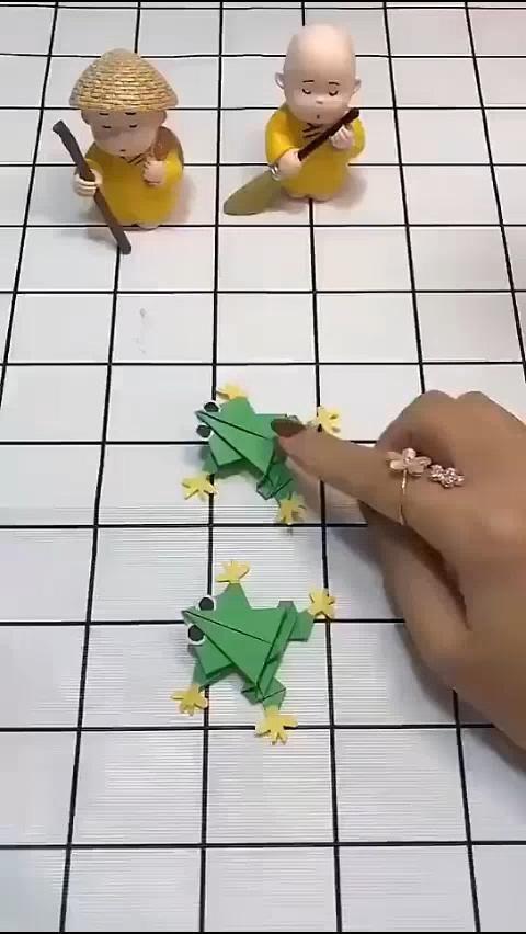 Photo of Origami. Green little frog. jump. jump. jump.
