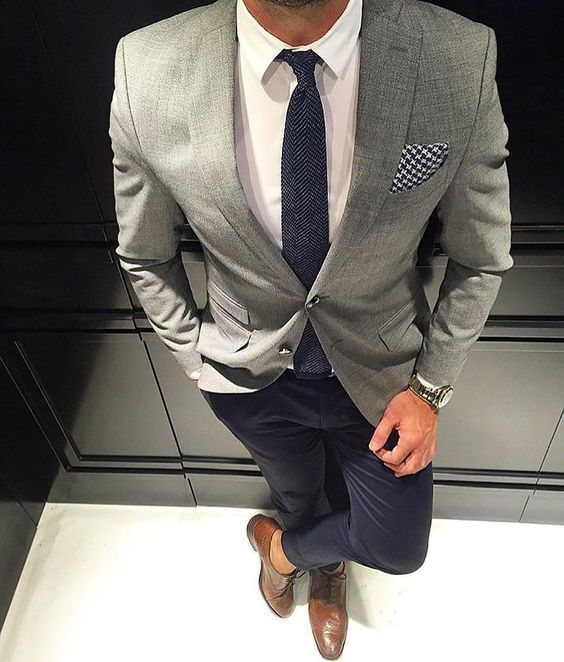 A smart casual combination of a grey coat and black chinos can maintain its relevance in many different circumstances. This outfit is complemented perfectly with brown leather brogues.   Shop this look on Lookastic: https://lookastic.com/men/looks/blazer-dress-shirt-chinos/24059   — White Dress Shirt  — Charcoal Herringbone Tie  — Black and White Houndstooth Pocket Square  — Grey Blazer  — Gold Watch  — Black Chinos  — Brown Leather Brogues