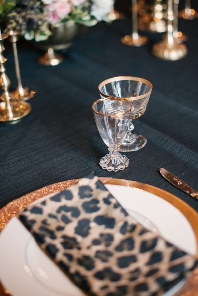 Animal prints over gold plates and black table cloth for a black and gold wedding & glittery new year\u0027s eve wedding | Printed napkins Place setting and ...