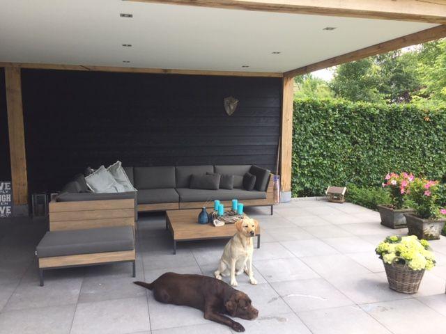 Luxe teakhouten loungeset met grijze kussens onder een overkapping