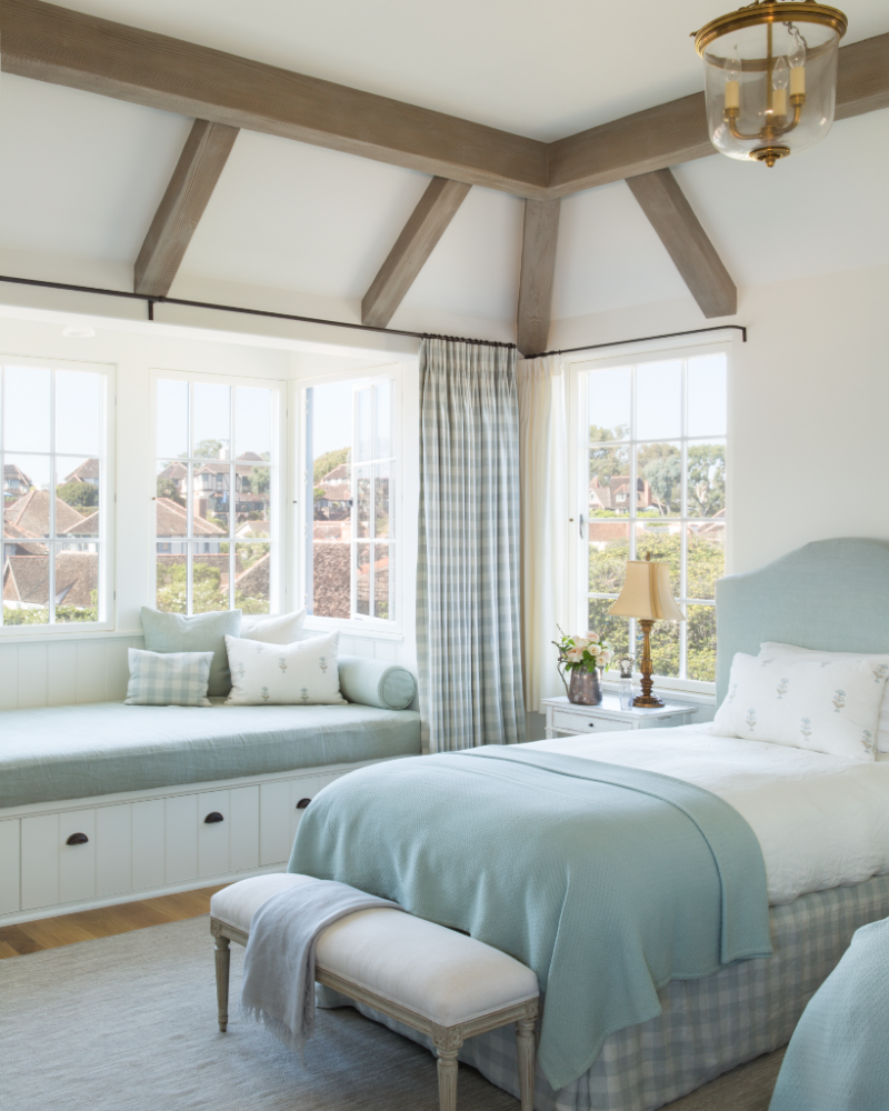 Patina style romantic bedroom - Feminine And Romantic Bedroom With Light Blue Check Drapes And Bed Skirts Window Seat Plaster Walls Rustic Wood Beams And White Oak Flooring In French