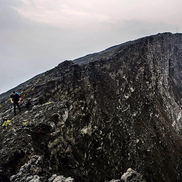 Photo by @petekmuller/@prime_collective. A hiker walks along the edge of the volcanic crater on the top of Mount #Nyiragongo in eastern DR #Congo. The summit stands at 11382 feet (3470m) and the main crater is approximately 2 kilometers wide. The last 300 meters of climbing are a bit of a scramble up trails of loose volcanic rock. At night the summit temperature hovers around or just below freezing. The hike to to top is only 5 miles (8 km) but the steep incline of the second half of the…