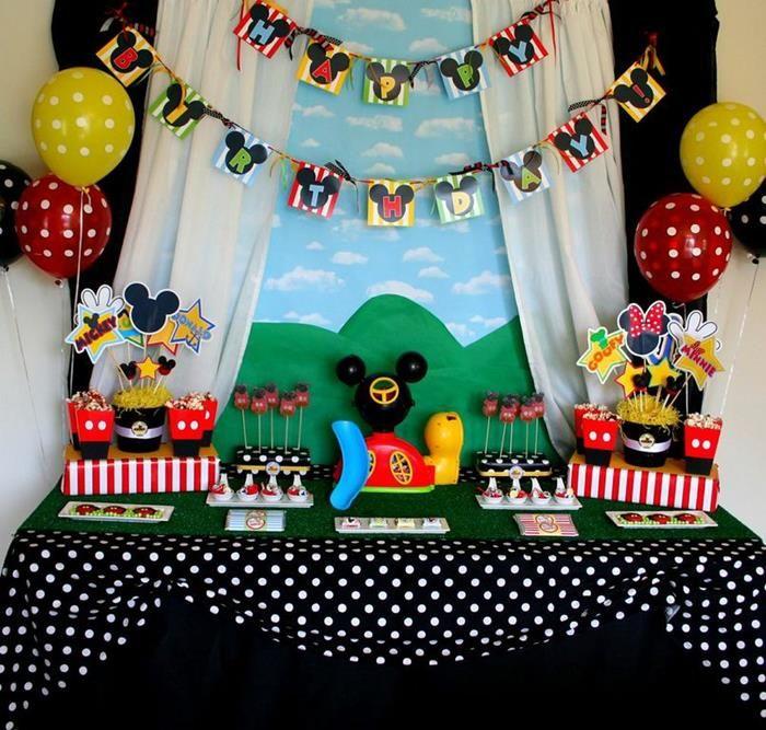 a toalha de bolinhas dá o tom divertido dessa mesa de bolo para festa com tema mickey