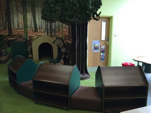 New library space with reading den, wooden bookcases and a tree centerpiece.  Southmead Primary School - Wimbledon, London. www.rapinteriors.co.uk