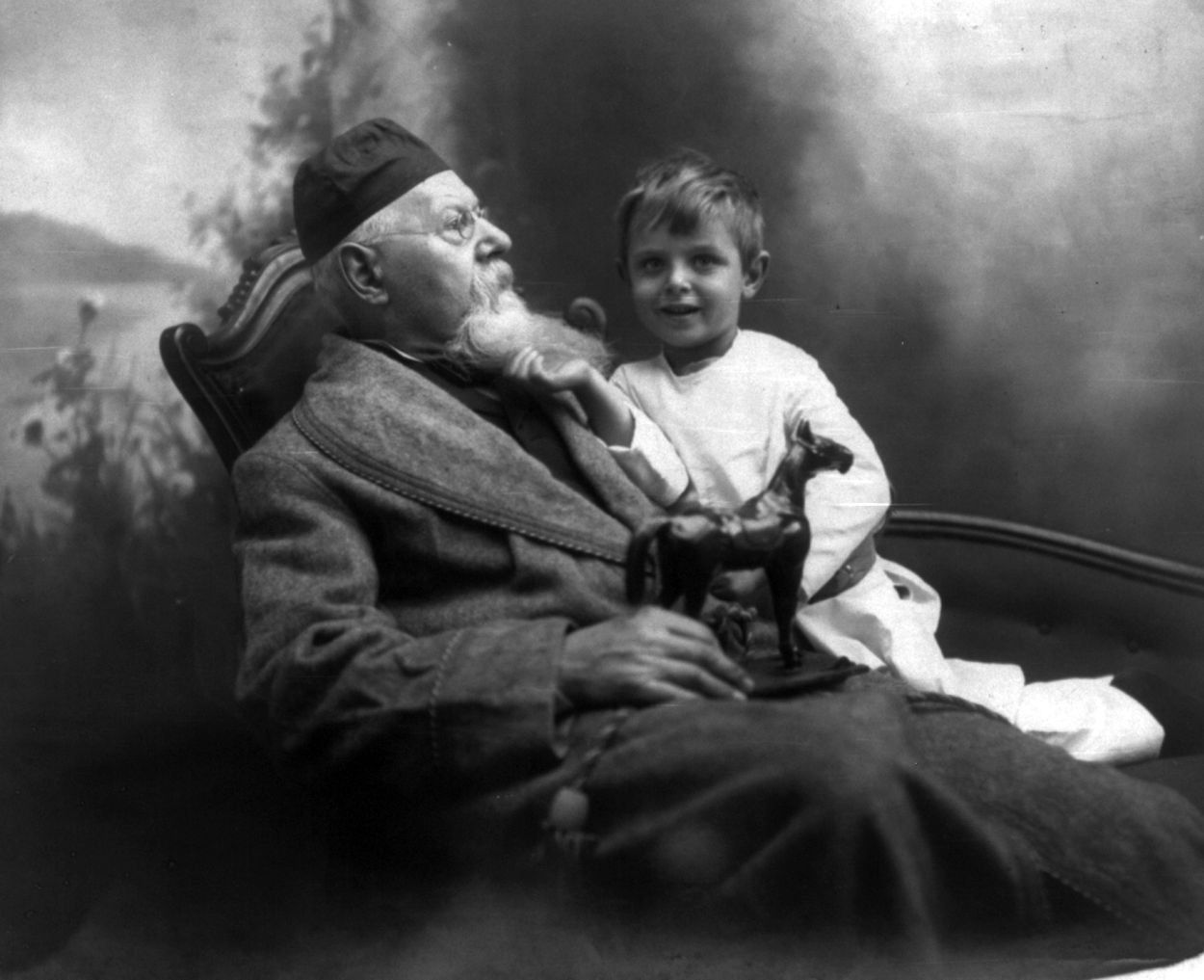 Christmas Morning. Summary: Elderly man seated, holding toy horse, facing right, with arm aroun ...