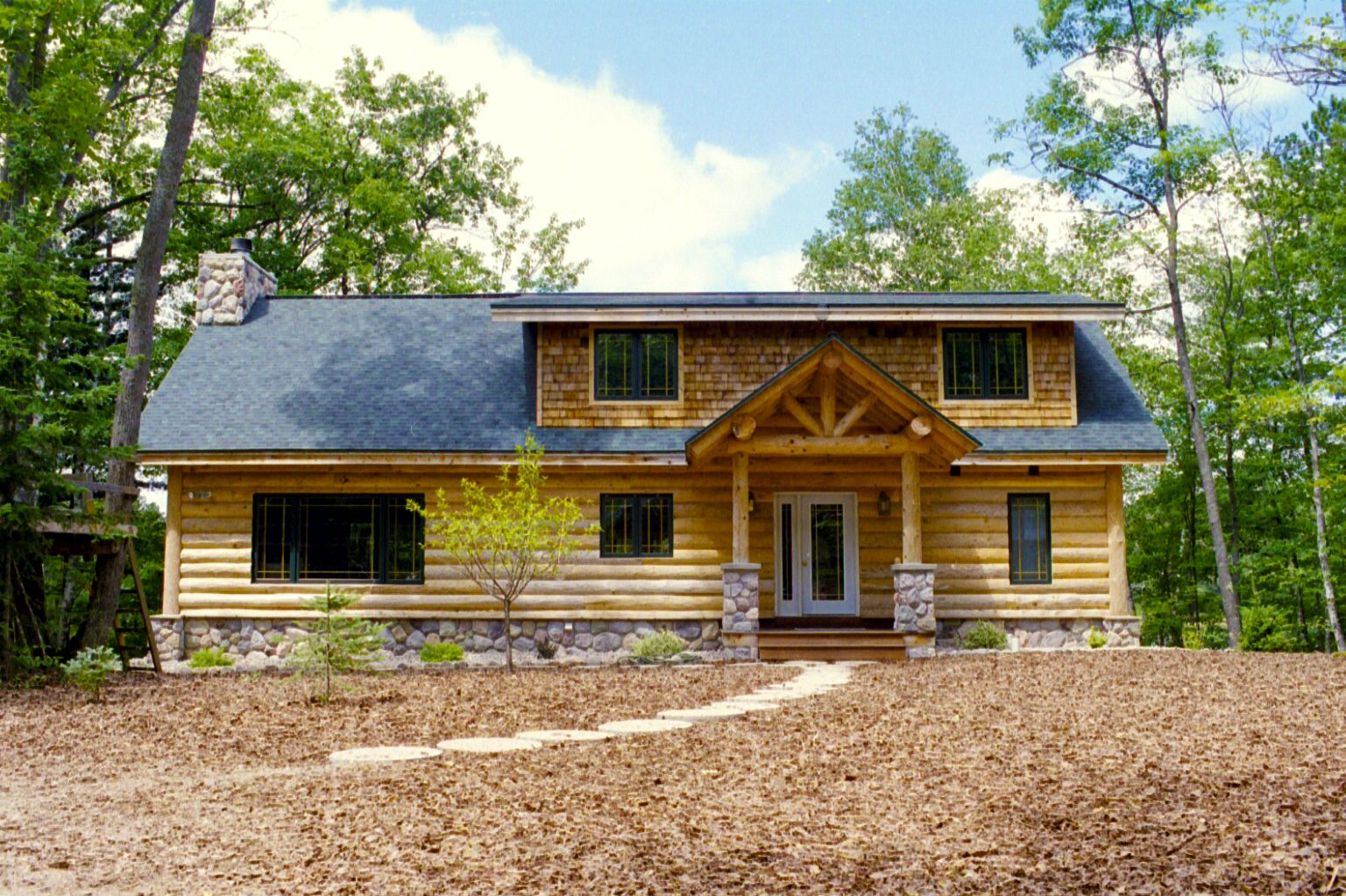a Chalet log cabin with stone accents and a log truss covered porch ...