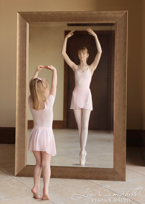 A mother and daughter pose as ballet dancers in front of a for Dance mirrors