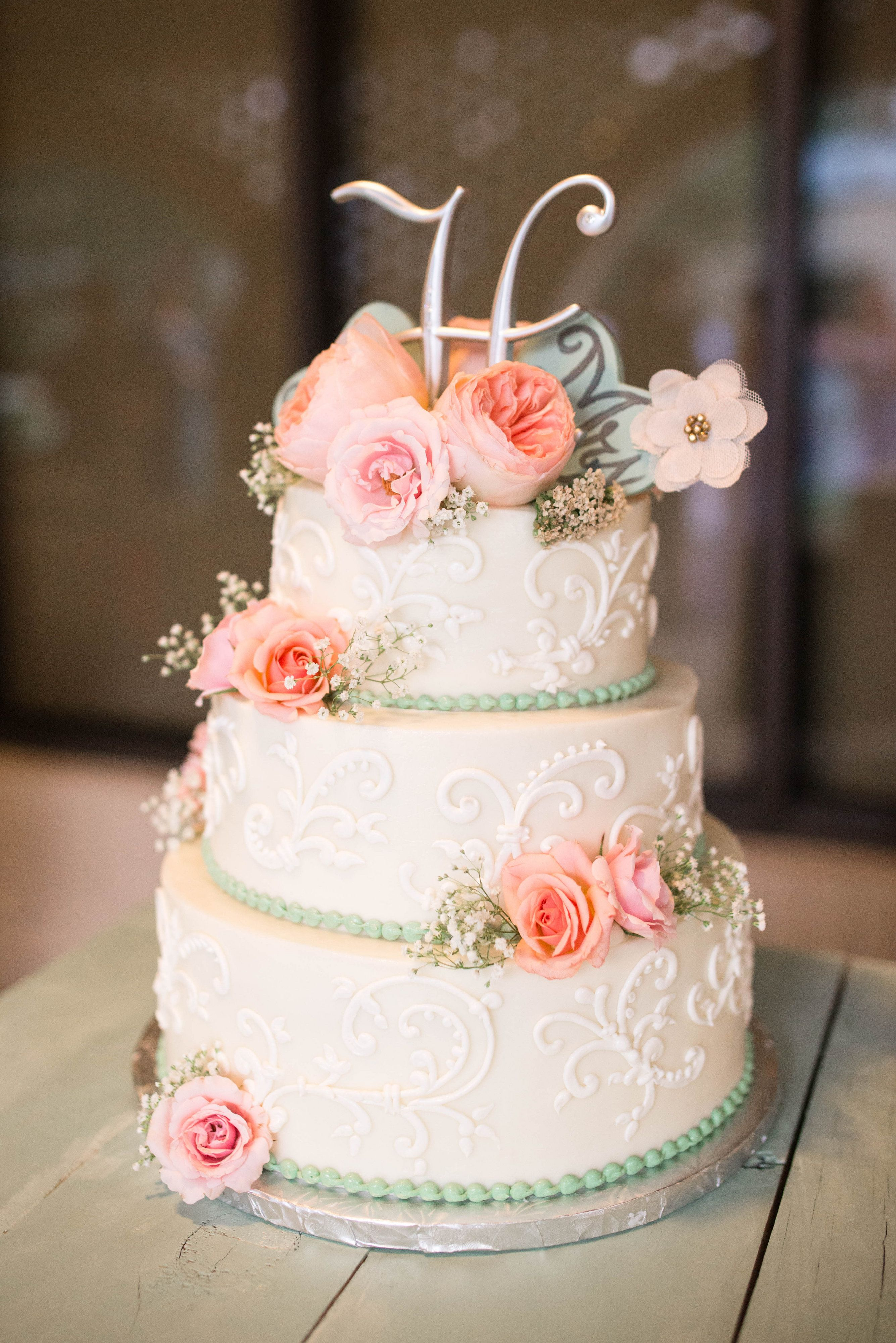 Three tier vintage inspired wedding cake with intricate piping and