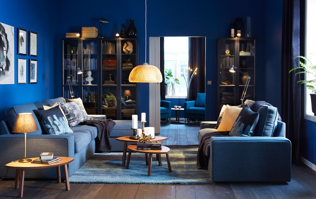 Blue living room with glass-fronted cabinets and two blue sofas, one ...