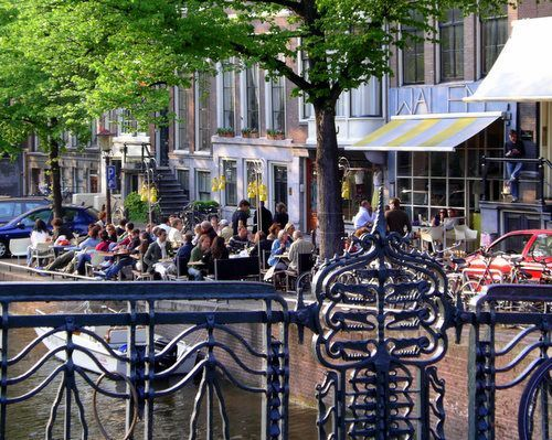 See where Amsterdam locals and visitors take part in the ritual of sitting on a café terrace, people-watching and enjoying fair weather. Beginning in early spring and stretching into late fall, cafés lure passers-by with seats in the sunshine. This photo gallery highlights some of the most idyllic café terraces in Amsterdam.