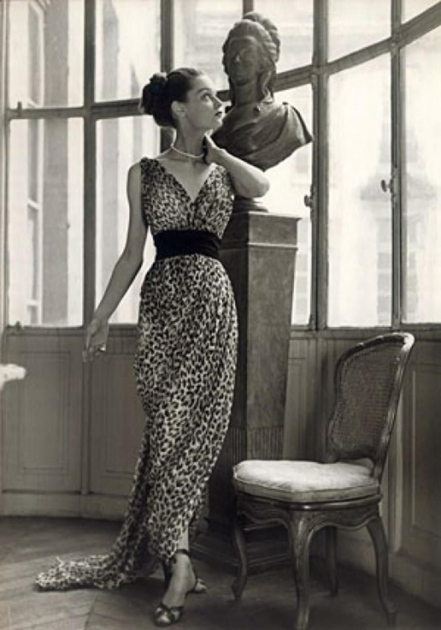 """Mitzah Bricard with sculpture, wearing a silk chiffon Christian Dior dress from the 1947 New Look Collection.  The first to recognize the leopard print as a reputable trend was Christian Dior. His iconic 1947 New Look collection """"featured two leopard dresses: the midi-length jungle sheath for day, and the silk chiffon Afrique gown for evening."""