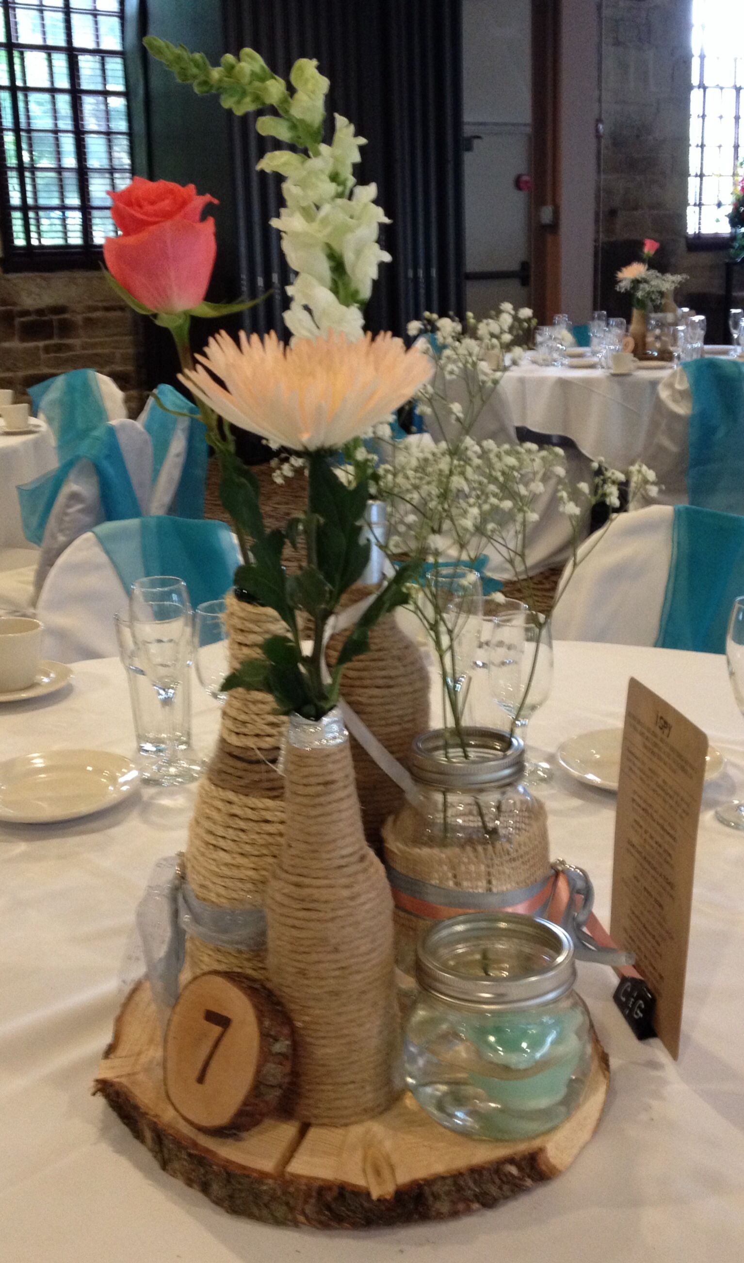 Rustic wedding centerpiece twine wrapped wine bottles