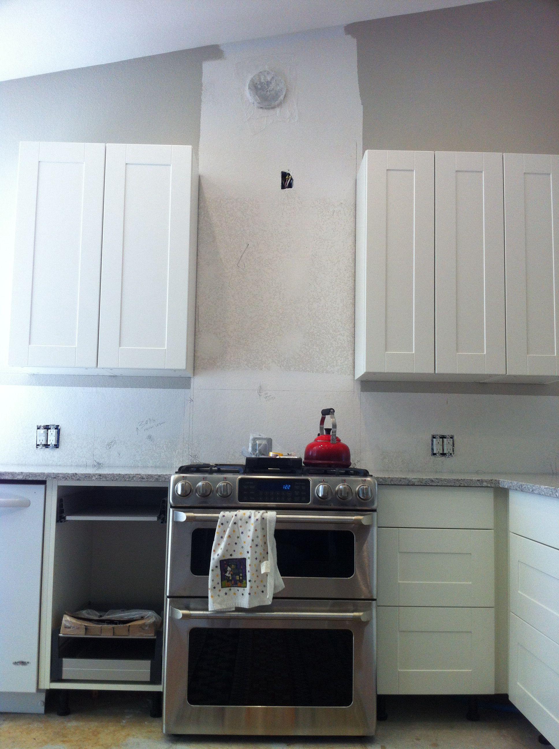 ikea cabinets with ge cafe double oven range. beveled subway tile